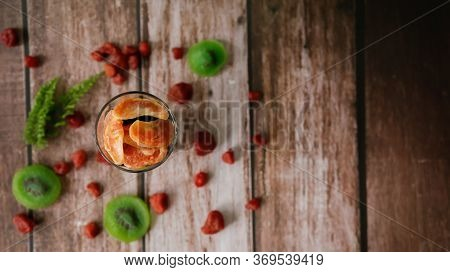Top View, Dried Orange In A Glass With Dried Kiwi Slices, Strawberry For  Blurred Background. Select