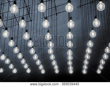 Ceiling Lamps Background. Unusual Ceiling. Soft Light Of Many Bulbs. Grey Faded Backdrop. Yellow Lig