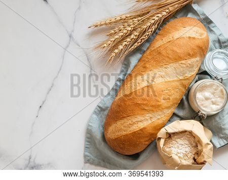 British White Bloomer Or European Sourdough Baton Loaf Bread On White Marble Background. Fresh Loaf