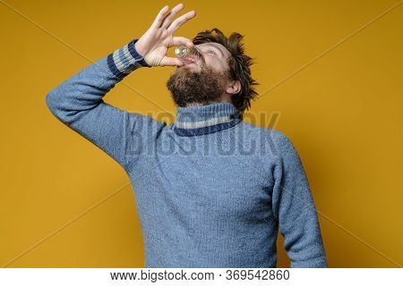 Shaggy, Bearded Man In A Sweater Drinks Strong Alcohol From A Wineglass, On A Yellow Background. Alc
