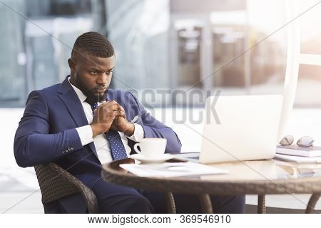 Coronacrisis And Bankruptcy. Thoughtful Black Businessman Sitting At Laptop Thinking How To Save Bus