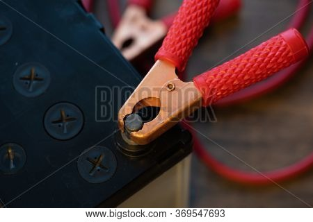 A Car battery with red battery jumper cable claw attached to the terminals.
