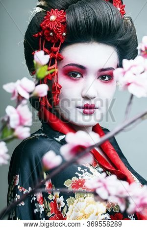 Young Pretty Geisha In Black Kimono Among Sakura, Asian Ethno Close Up