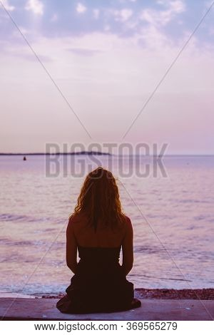 Woman Silhouette Sitting On The Beach Looking At Sunset Over The Sea