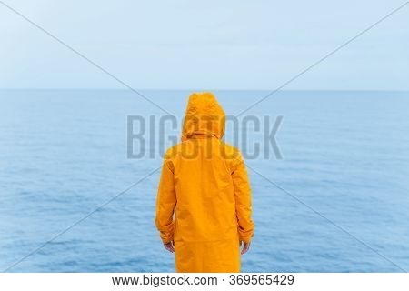 Woman In Yellow Raincoat At Sea Beach Cliff At Storm Rainy Weather