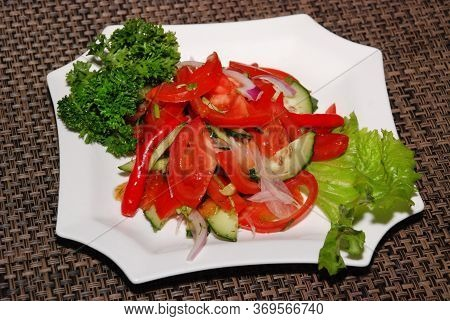Served Vegetable Salad With Tomatoes On The White Plate
