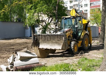 The Yellow Bulldozer Excavator Is Located In The Courtyard Of A Multi-storey Multi-apartment Buildin