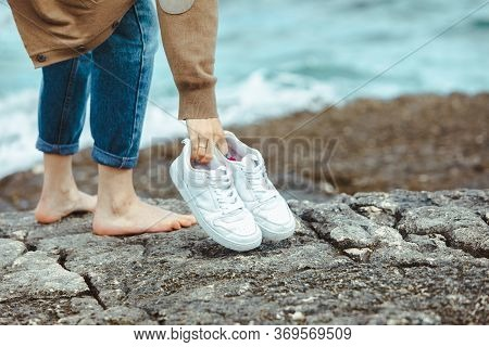 Woman Walking Barefoot By Seaside Holding Hands White Shoes. Summer Vacation