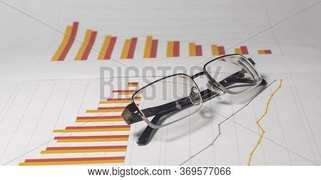 Eyeglasses On Business Chart Diagram Graph Of Falling Trend In Red And Orange Colors. Data Analyzing