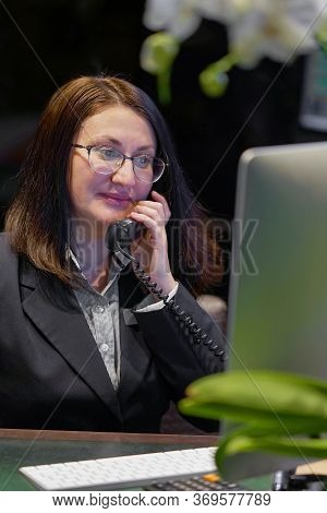 Woman Answers Customer Calls In A Call Center. The Secretary Answers The Phone And Talks With Client