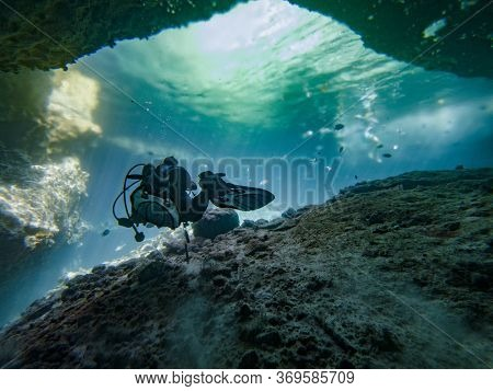 Photo Of A Scuba Diver Swimming On Tropical Crystal Clear Water In A Cave At Sunny Summer.