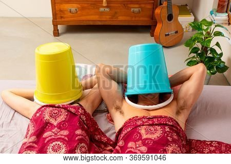 Young couple in bed with a bucket on their heads, they make love or rest, however they don't talk to each other.