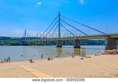 Novi Sad, Serbia - July 3, 2019: People Enjoy On A Beach On A Danube River, View At Liberty Bridge I
