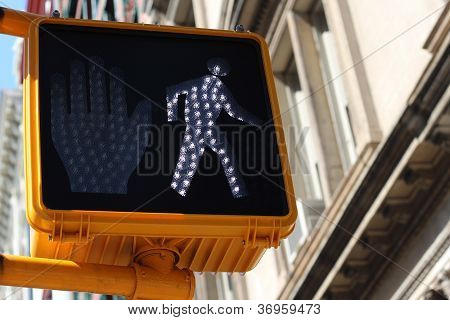 Green pedestrian signal with a little walking man indicating that it is safe to cross the intersection or crossroads poster