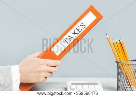 Close Up Of Hand Holding Taxes Binder In Business Office Space. Bookkeeper Or Accountant With Calcul