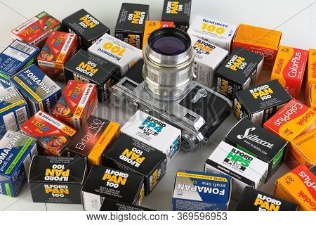Film Packings Lford And Kodak For Old 35 Mm Slr Camers On White Cement Background.