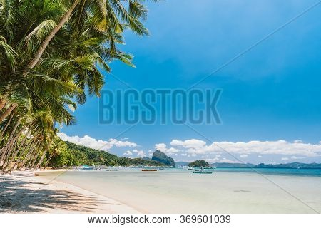 Palm Trees Of Corong Corong Beach With Traditional Boats And Blue Sky In El Nido, Palawan Island, Ph