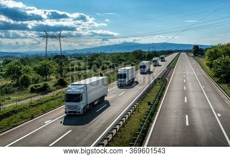 Fleet Of Light Blue Transportation  Trucks In Line As A Caravan Or Convoy On A Country Highway Under