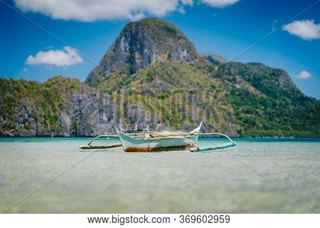 Boat On Ocean Water Surface In El Nido Bay And Cadlao Island In Background, Palawan, Philippines
