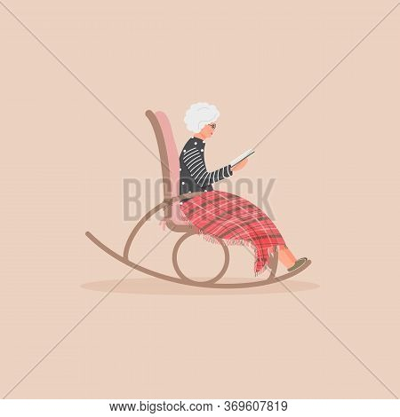 Elderly Cute Woman Is Sitting In A Rocking Chair.old Lady Covered Her Feet With Checked Woollen Plai