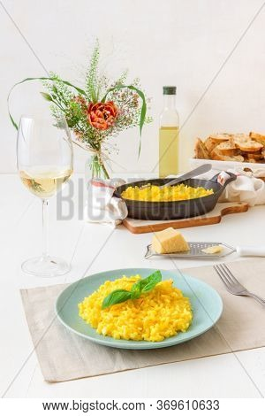 Risotto Milanese, Wooden Table With Traditional Italian Saffron Risotto, Glasses And Pitcher Of Wine