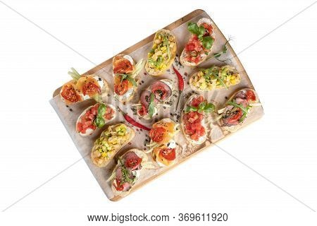 Assorted Bruschett On A Wooden Board. Isolated On A White Background.