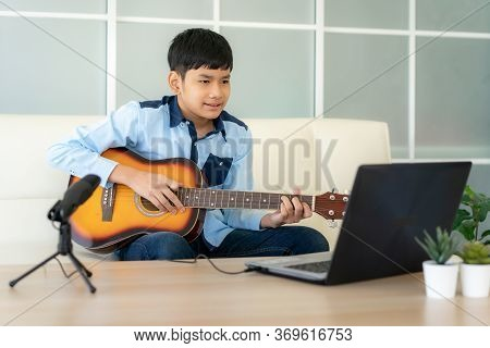 Asian Boy Playing Acoustic Guitar And Watching Online Course On Laptop While Practicing At Home. Asi