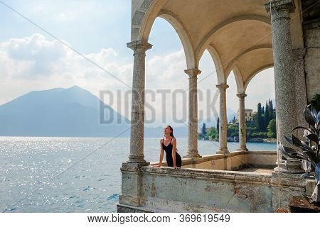 A Young Woman In A Black Dress Standing On The Old Balcony Of Villa Monstera Looking At The Lake Com
