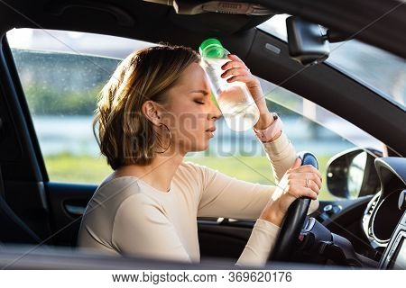 Exhausted Woman Driver Feeling Headache, Sitting Inside Her Car, Applies A Bottle Of Water To His Fo