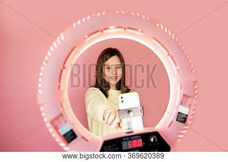 Young Beautiful Brunette Girl Leading Her Daily Vlog Online On The Pink Background. Copy Space. Self