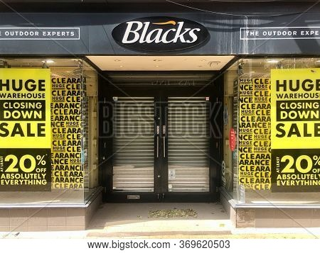 READING, UK - MAY 24, 2020: Security shutters behind the doors to Blacks outdoor clothing retailer during the Covid-19 pandemic on the high street in Reading, Berkshire, UK.
