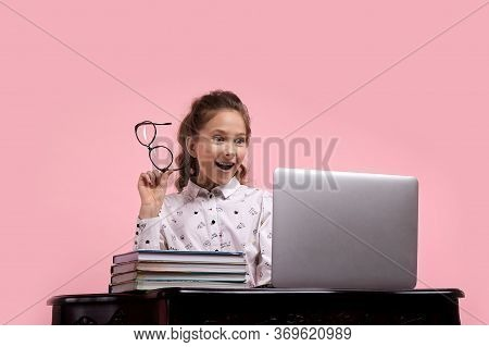 A Girl Holds Glasses In Her Hand And Looks With Enthusiasm At The Laptop Screen.
