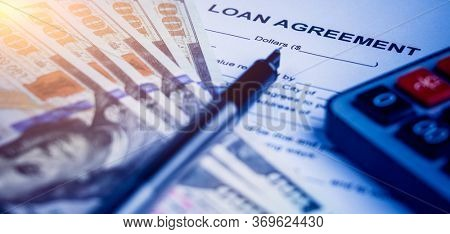 loan agreement with calculator and money on desk.