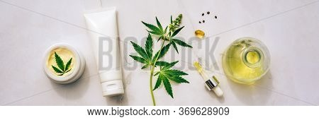 Tuba And Jar Of Cream Cbd Oil, Thc Tincture And Hemp Leaves On Marble Background. Flat Lay, Minimali