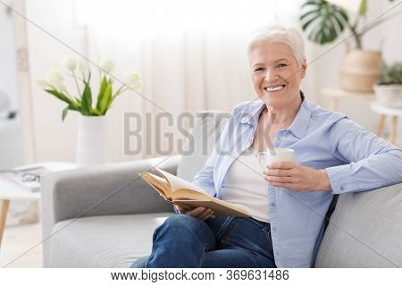 Favorite Pastime. Positive Senior Woman Relaxing With Book And Hot Tea On Couch At Home And Smiling