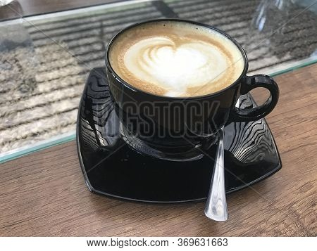 Black Cup With Capuccino With A Heart Shape And Some Grains In The Background
