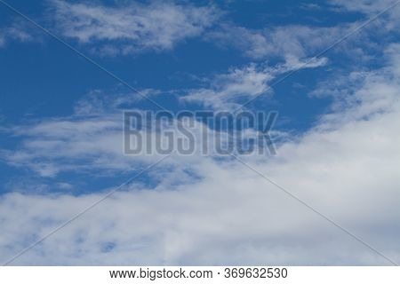 The Background Is A Blue Sky With White Clouds