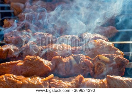 Meat On Grill. Morning Bbq. Cooking Barbecue On The Grill With Smoke. Cook Fresh Marinated Meat With