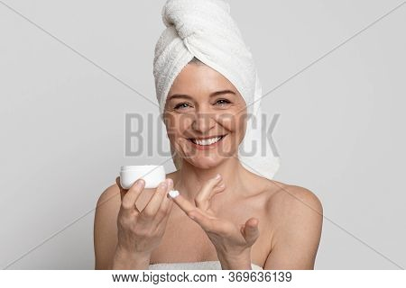 Positive Mature Woman With Towel On Head Holding Jar With Moisturising Anti-aging Cream, Pampering H