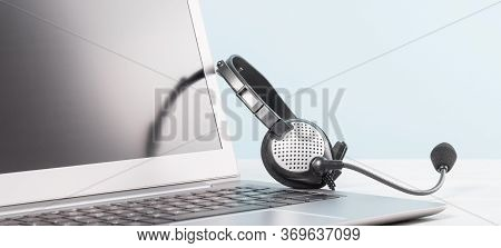 Part Of Laptop With Blank Screen With Headphones On Desk Blue Background. Copy Space. Distant Learni