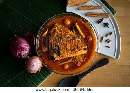 Malaysian Traditional Dish, Fish Head Curry Served On Banana Leaf With Various Ingredients Spices .