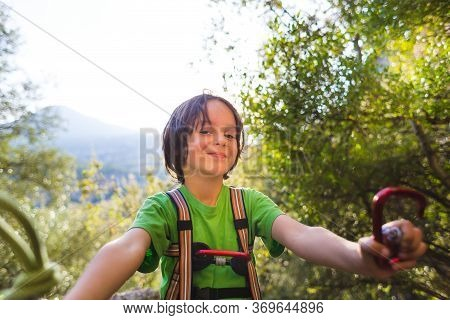 The Child Shows A Knot Of Rope And A Carabiner. Climbing Rope For Belaying. A Little Boy Is Trying T