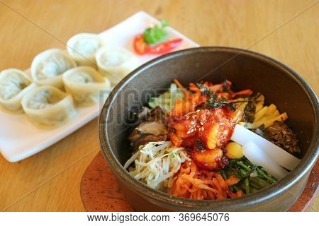 Mouthwatering Bibimbap Or Korean Mixed Rice Bowl With Blurry Mandu Dumplings In Background