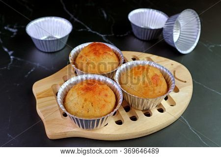 Homemade Banana Muffins In Mold On Wooden Bread Board With Empty Aluminum Muffin Mold On Kitchen Bla