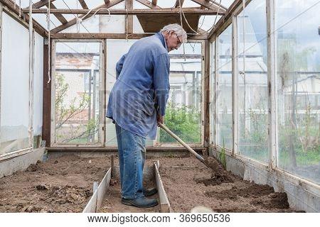 Cheerful Senior Elderly Man Digging Garden Spring Time