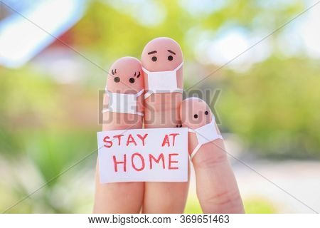 Fingers Art Of Family With Face Mask Is Sitting In Quarantine At Home. People Hold Placard Stay At H