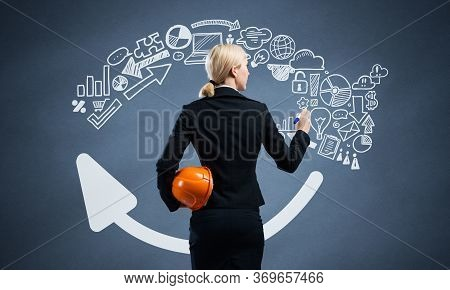Businesswoman Draws Arrows Consists Of Business Doodles On Blackboard. Back View Woman With Safety H