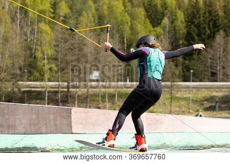 Fagersta, Sweden - Maj 26, 2020: Wakeboarder Teen Girl Make An Extreme Jump On Wakeboard, Around The