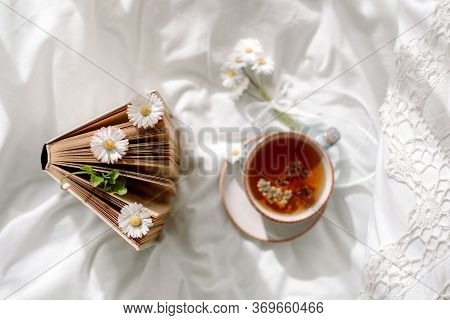 A Cup Of Coffee And An Open Book On White Open Bed. Top View.morning Breakfast. Bright Cozy Day
