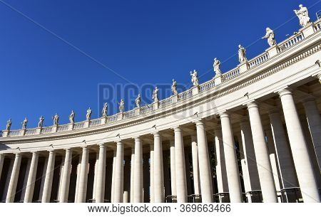 Berninis Colonnade And Statues At St. Peters Square With Blue Sky. Vatican City, Rome, Italy.